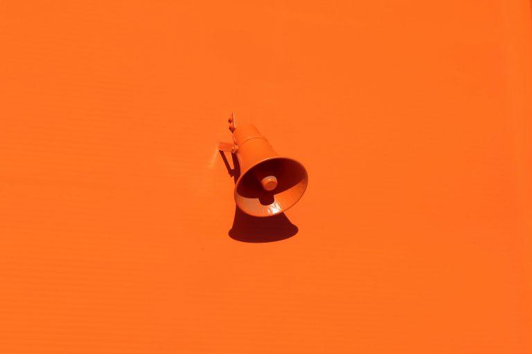 Pared naranja con megáfono