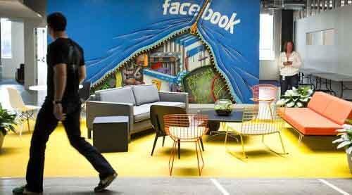 Una pared donde se lee Facebook y hay unos sillones delante